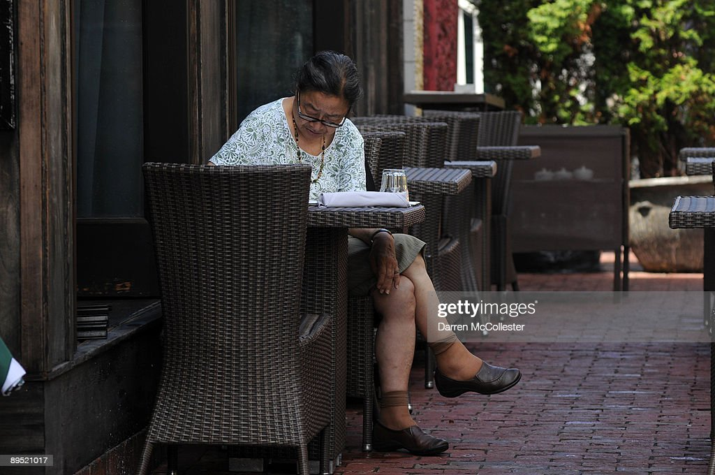 A woman sits at an outdoor table at OM Restaurant just after a rainstorm July 30, 2009 in Harvard Square in Cambridge, Massachusetts. Harvard Square is a large triangular area located in the heart of Cambridge and adjacent to Harvard University, and is frequented by tens of thousands of tourists a year, and home to thousand of students with MIT University just down the road.
