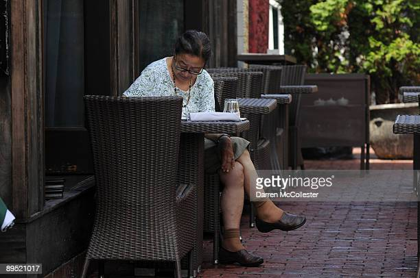 A woman sits at an outdoor table at OM Restaurant just after a rainstorm July 30 2009 in Harvard Square in Cambridge Massachusetts Harvard Square is...