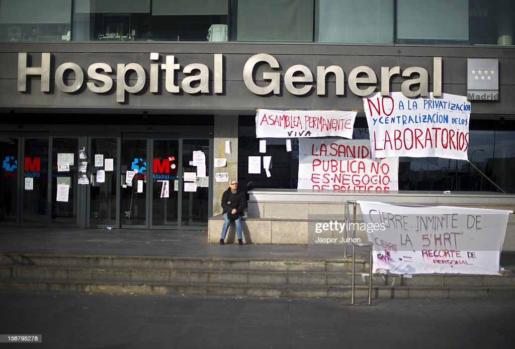 A woman sits besides banners at the entrance of La Paz hospital on November 21, 2012 in Madrid, Spain. Doctors and nurses in the Spanish capital are preparing for a four day strike to protest against the privatisation of some parts of Spain's national health service.