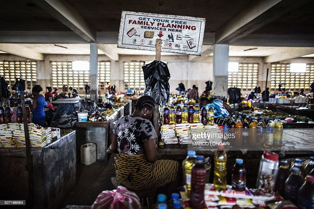 A woman sits by her stall in the Jorkpan market at Sinkor district in Monrovia, on May 2, 2016. Family planning services, like contraceptives and counselling are available in the markets in Liberia, an initiative that is aimed at tackling the high adolescent pregnancy rate in the younger population. / AFP / MARCO