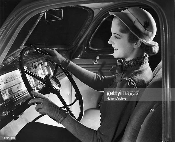 A woman sits cheerfully behind the wheel of an automobile She wears a hat and driving gloves