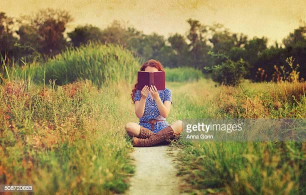 Woman sits cross-legged on path reading book