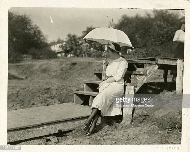 A woman sits enjoying the outdoors while shading herself from the sun with a light colored umbrella Cincinnati OH ca 1905
