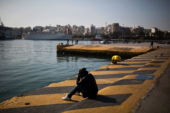 TOPSHOT - A woman sits facing the sea outside a passenger terminal used as a shelter for refugees and migrants at the Piraeus harbour in Athens on March 21, 2016. A total of 1,662 migrants have lan...