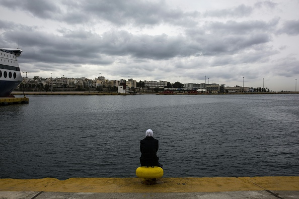 A woman sits facing the sea outside a passenger terminal used as shelter for refugees and migrants at the Piraeus harbour in Athens on March 12, 2016