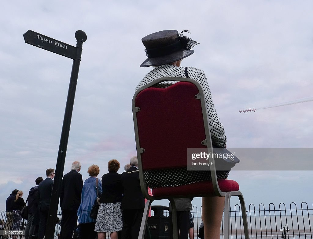 A woman sits in a chair and watches a display by the RAF Red Arrows during the Armed Forces Day National Event on June 25, 2016 in Cleethorpes, England. Armed Forces Day is an annual event that gives an opportunity for the country to show its support for the men and women in the British Armed Forces. The visit by Prime Minister David Cameron to the event came the day after the country voted to leave the European Union.