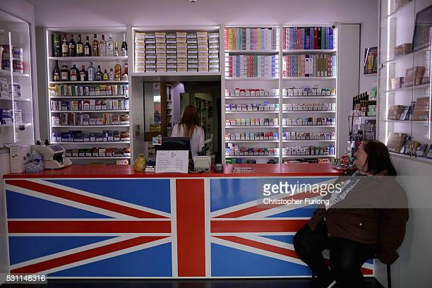 A woman sits in a discount tobacco shop catering for cross border travellers on May 10 2016 in Adinkerke Belgium The Schengen Agreement which led to...