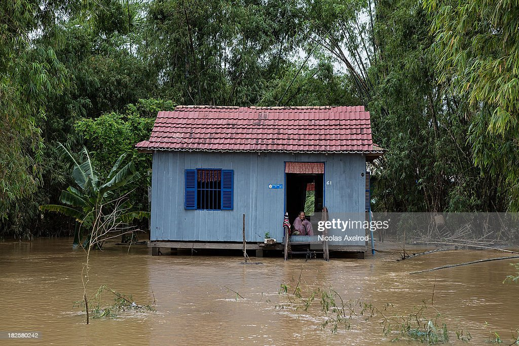 A woman sits in a flooded house in Tonle Bit commune, as 500 families are relocated from Tonle Bit commune after the Mekong river broke it's banks on October 1, 2013 in Kampong Cham Province, Cambodia. Recent flooding has so far claimed the lives of 30 people, and 30,000 homes have been affected across eight different provinces throughout Cambodia.