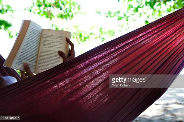 A woman sits in a hammock and reads a book on the beach front on the island of Koh Lipe in Satun province in Southern Thailand Located close to...