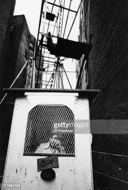 A woman sits in a kiosk outside the 'Shrine Church of Saint Anthony of Padua' Sullivan Street New York City 1973