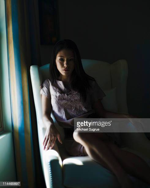 A woman sits in a loveseat next to a window.