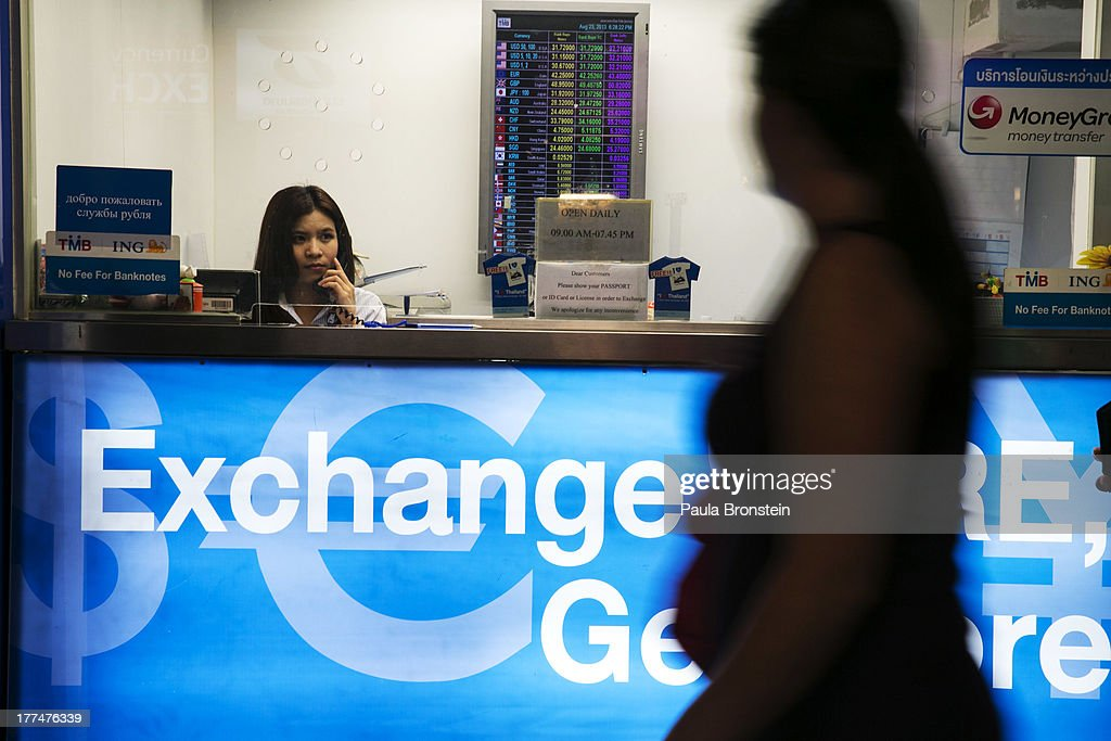 A woman sits in a money exchange bank kiosk on August 23, 2013 in downtown Bangkok, Thailand. The local currency dropped to its lowest level since August 2010. Against the US dollar the Thai baht fell to 32.09/32.13 dropping about 5% this year.