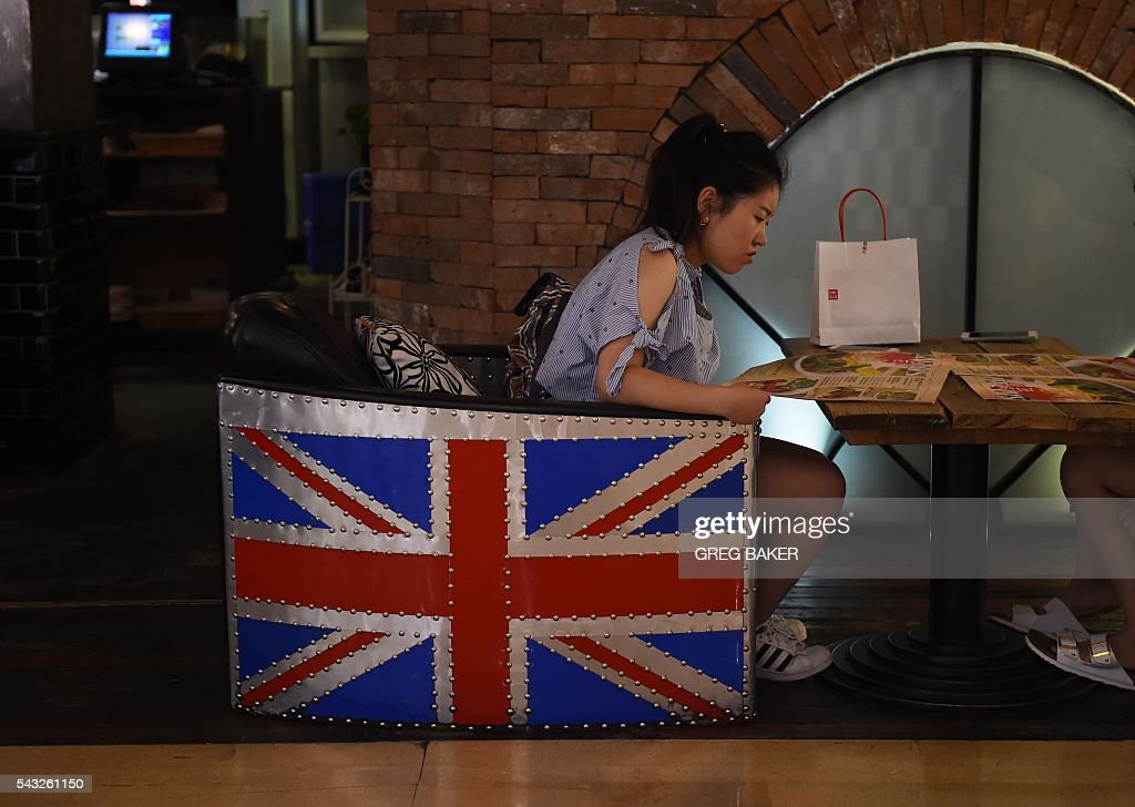 A woman sits in a restaurant chair decorated with the British flag in Beijing on June 27, 2016. Britain's vote to leave the European Union has added new uncertainties to the world economy at a time when downward pressures on China's economy are mounting, Premier Li Keqiang said on June 27 at a World Economic Forum meeting in the Chinese city of Tianjin. / AFP / GREG