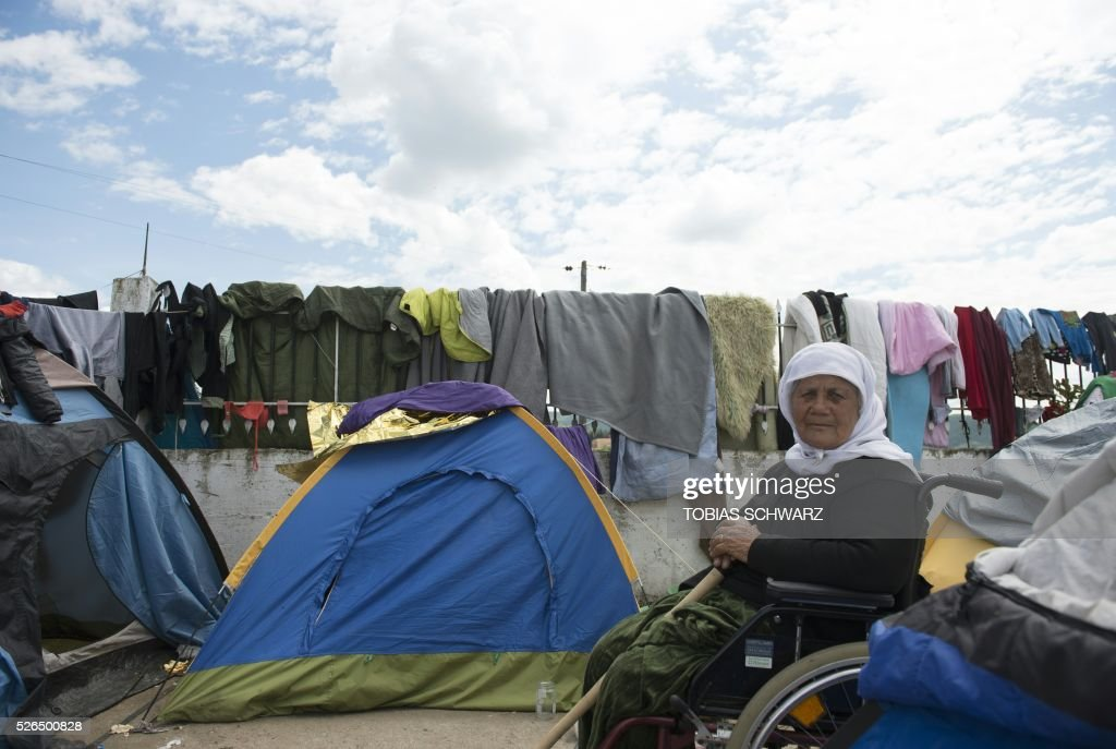 A woman sits in a wheelchair surrounded by tents and drying clothes at a makeshift camp for migrants and refugees near the village of Idomeni not far from the Greek-Macedonian border on April 30, 2016. Some 54,000 people, many of them fleeing the war in Syria, have been stranded on Greek territory since the closure of the migrant route through the Balkans in February. / AFP / TOBIAS