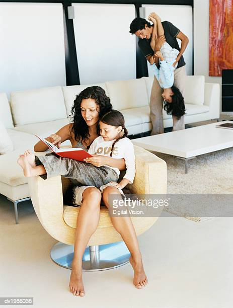 Woman Sits in an Armchair With Her Daughter on Her Lap, Reading a Book to Her, Dad and Sister in the Background