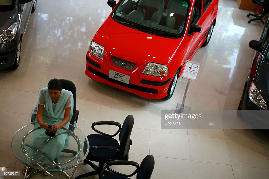 A woman sits in an car dealership , on April 14, 2008 in Bangalore, India. Many residents work for multi-national cooperations and the economy is booming. New construction for offices is under way. Shopping malls open frequently and the shops are full of western merchandise for workers with high disposable income. India's new middle class is about 300 million, and growing.
