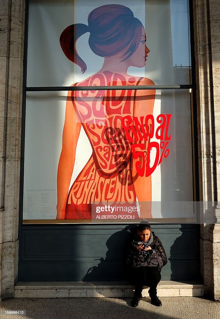 A woman sits in front of a shop advertises its sale, on January 5, 2013 during the first day of sales in Rome.