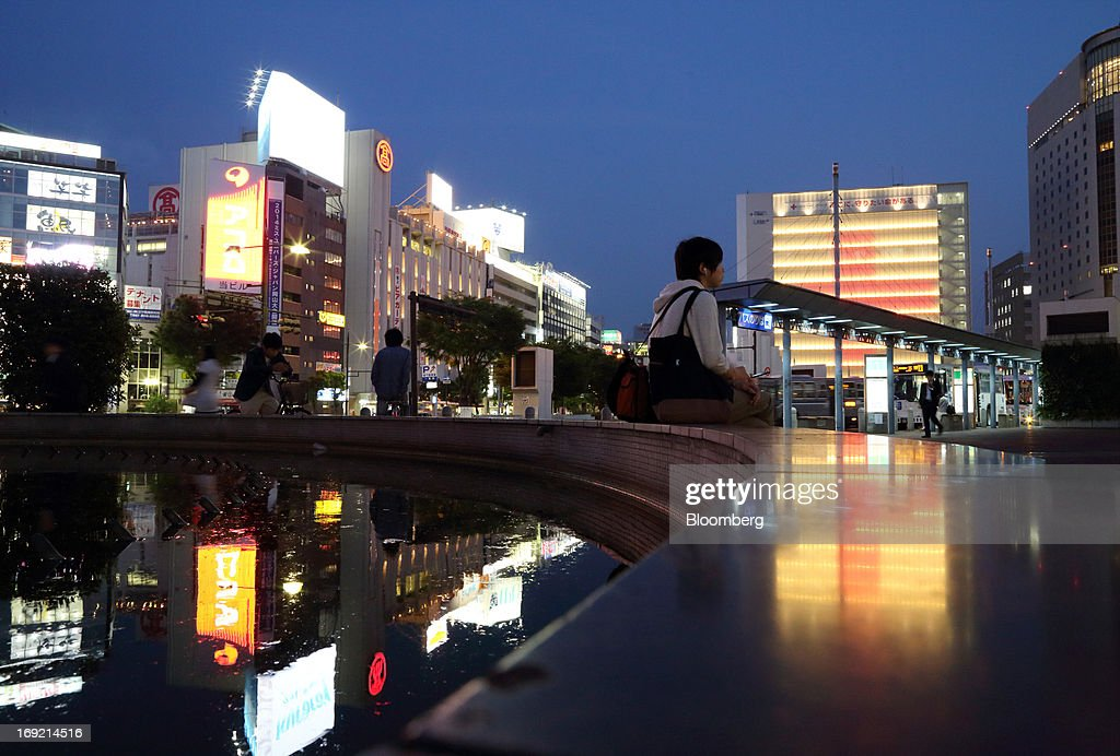 A woman sits in front of buildings outside Okayama train station at night in Okayama, Japan, on Monday, May 20, 2013. The Bank of Japan, forecast to maintain plans for expanded monetary easing at a meeting ending on May 22, is targeting 2 percent inflation in two years after more than 10 years of entrenched deflation. Photographer: Tomohiro Ohsumi/Bloomberg via Getty Images