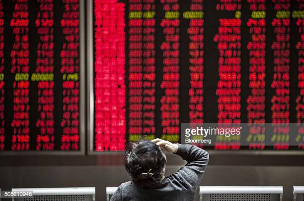 A woman sits in front of electronic boards displaying stock information at a securities brokerage in Beijing China on Monday Jan 18 2016 China's...