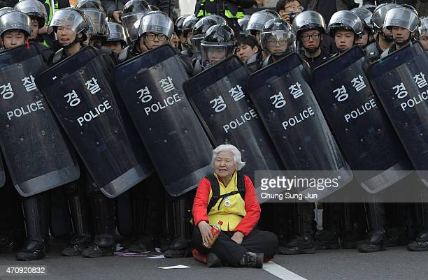 A woman sits in front of riot police blocking the road to protect protesters during the antigovernment protest on April 24 2015 in Seoul South Korea...