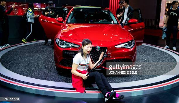 A woman sits in front of the new Guilia Milano car from Italian car maker Alfa Romeo during the first day of the 17th Shanghai International...