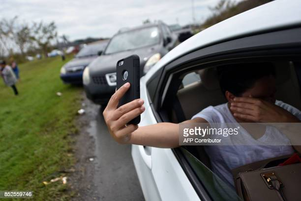 A woman sits in her car and tries to make a cellphone call on a highway near Dorado 40 km north of San Juan Puerto Rico on September 23 2017...