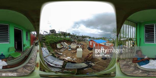 A woman sits in her hammock as damaged homes and debris stand in an area without electricity on October 15 2017 in San Isidro Puerto Rico Puerto Rico...
