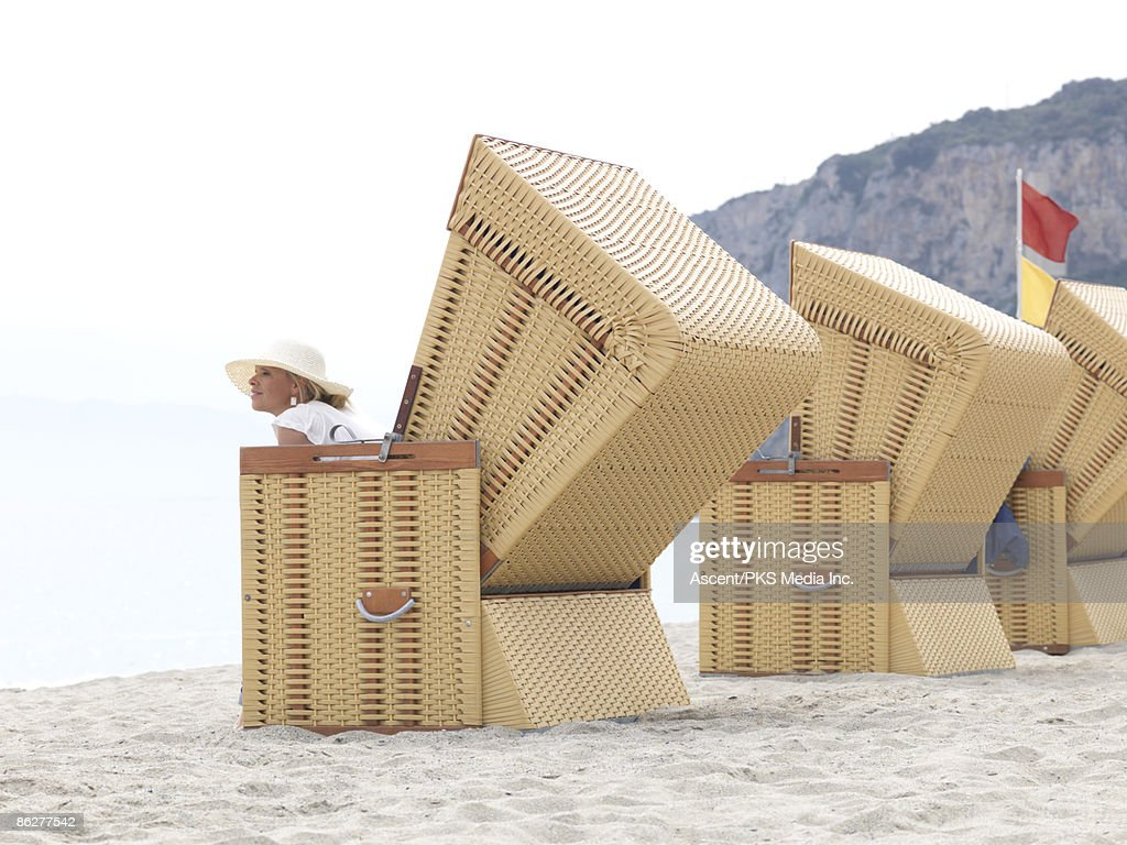 Woman sits in large beach chair, looks out : Stock Photo