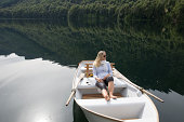 Woman sits in rowboat with smart phone, contemplat