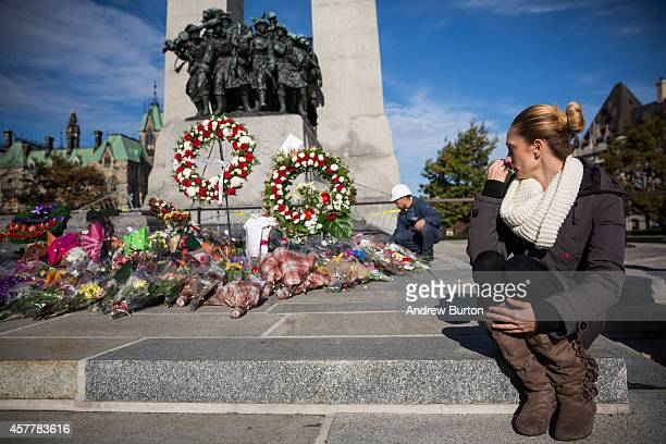 A woman sits in silence while paying her respects to Cpl Nathan Cirillo of the Canadian Army Reserves who was killed two days ago while standing...