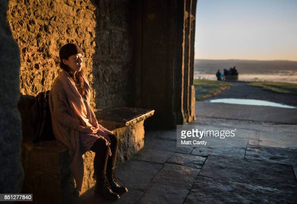 A woman sits in sunlight as the autumn sun rises over the Somerset Levels viewed from Glastonbury Tor near Glastonbury on September 22 2017 in...