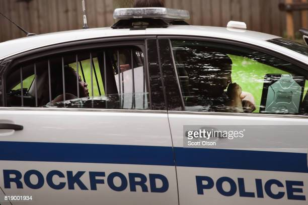 A woman sits in the back of a squad car after she was taken into custody for fighting outside of a suspected drug house on July 12 2017 in Rockford...