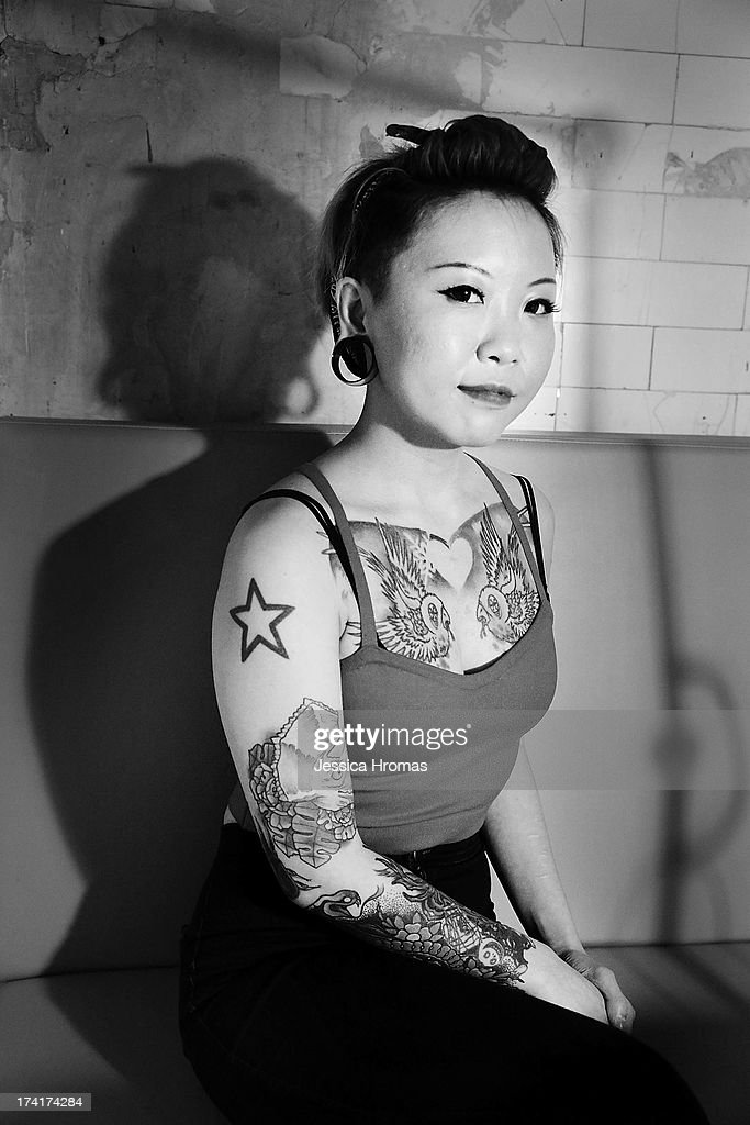 A woman sits in the free tattoo booth during the Dirty Boogie Rockabilly Festival at the Fringe Club on July 20, 2013 in Hong Kong, Hong Kong.