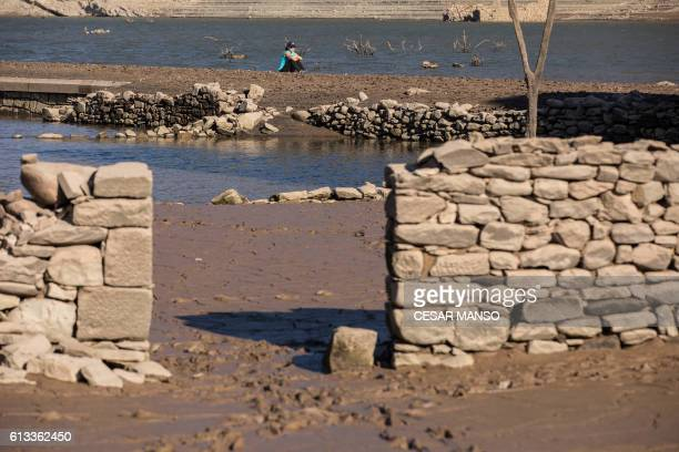 A woman sits in the remains of the former town of Mansilla on October 8 2016 after the village emerged from the depths of the Mansilla Reservoir as...