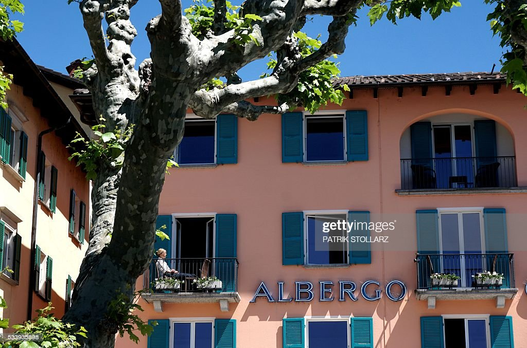 A woman sits in the sun on a balcony in the town of Ascona on Lago Maggiore also called Lake Langen on May 24, 2016. The German national football team will train here from May 24 until June 3, 2016 for the EURO 2016 taking place in France. / AFP / PATRIK