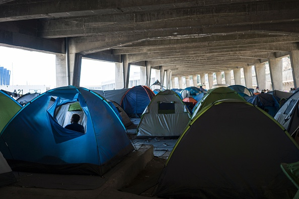 A woman sits inside her tent at the port of Piraeus, where nearly 1,500 refugees and migrants live at a makeshift camp or in passenger areas, in Athens on July 3, 2016