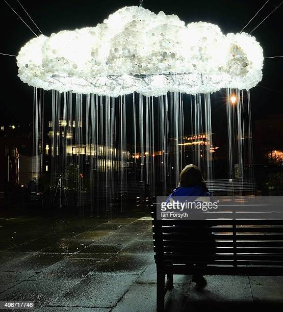 A woman sits looking at a spectacular light display called 'Cloud' during a preview night ahead of the Lumiere light event on November 11 2015 in...