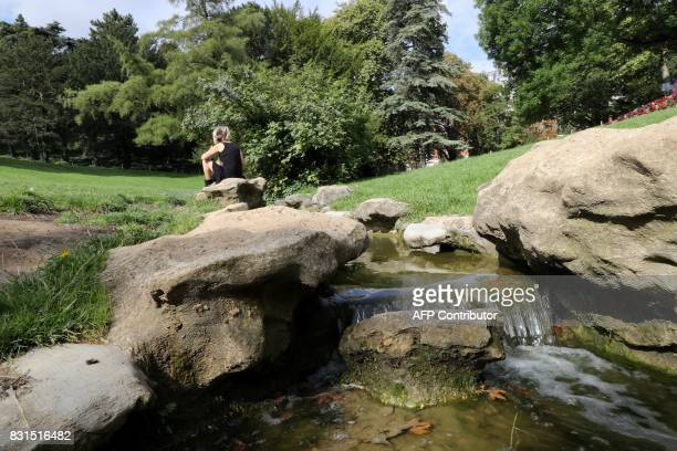 A woman sits near a stream in the ButtesChaumont Park in Paris on August 13 2017 The ButtesChaumont Park created in 1867 celebrates its 150th...