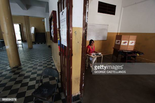 A woman sits next to a ballot box in a polling station during Venezuela's municipal elections in San Cristobal Tachira state on December 10 2017 /...
