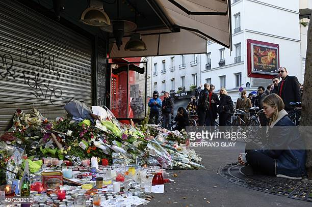 A woman sits next to a memorial site of flowers and candles on November 15 outside of the Le Belle Equipe in the 11th district of Paris for victims...