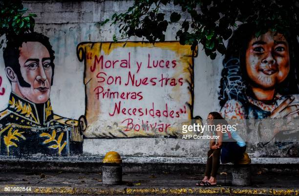A woman sits next to a mural depicting Latin American liberator Simon Bolivar and one of his quotes 'Morality and Enlightenment Are Our Prime...