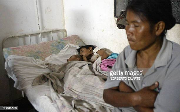 A woman sits next to her sons on a hospital bed after they became sick for drinking dirty water from a water pool in Cruce Pioneros some 400 km north...