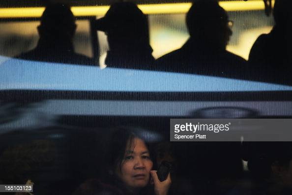 A woman sits on a bus going to Manhattan after waiting hours in Brooklyn as the city continues to recover from superstorm Sandy on November 1 in New...
