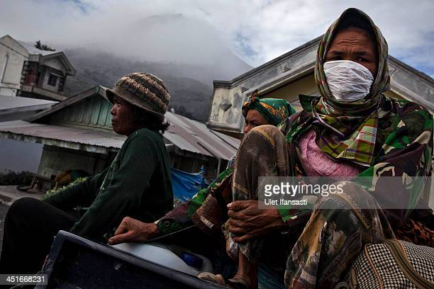 SUKANALU SUMATRA INDONESIA NOVEMBER 24 A woman sits on a car as she evacuates to a temporary evacuation center following another eruption of Mount...
