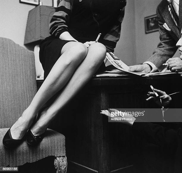 A woman sits on a desk during a meeting with two colleagues circa 1960