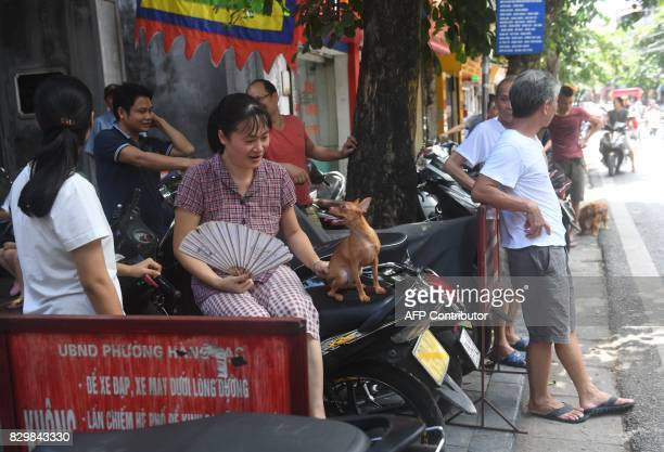 A woman sits on a shooter with a dog as residents wait outside their homes while municipal workers spray chemicals to kill mosquitos inside the...