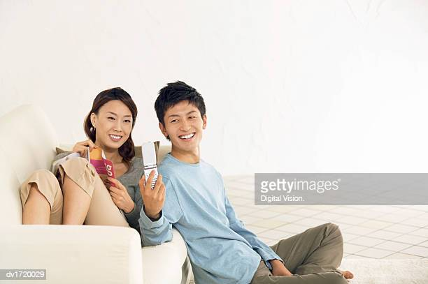 Woman Sits on a Sofa, Her Boyfriend Sitting on the Floor Taking a Picture of Her With His Mobile Phone