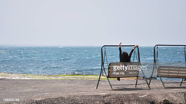 woman sits on a swing by the sea