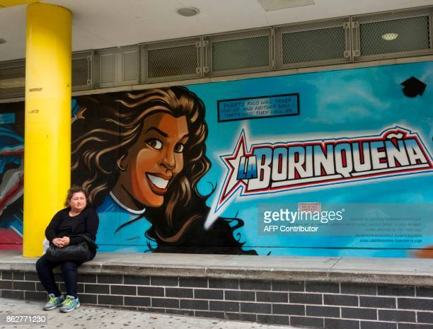 A woman sits on a wall at the Casita Maria Center for Arts Education in New York City in front of a mural of the bestselling graphic novel La...