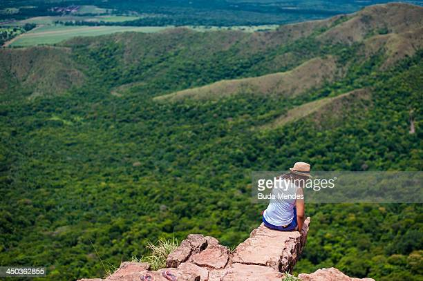 A woman sits on an outcrop and enjoys the view of the Chapada dos Guimaraes on November 17 2013 near Cuiaba Brazil The area is constituted as a...